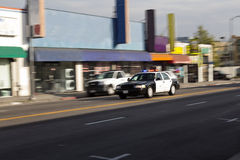 Lumières simples de voiture de police descendant la rue Image stock