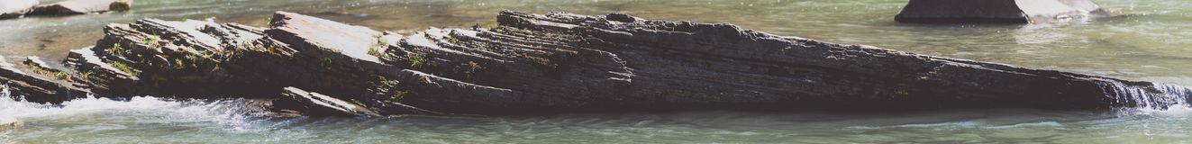 Lump of argillite along the river. Wide mineral texture background stock photos