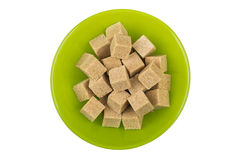 Lump brown cane sugar in shiny green glass plate Stock Photos
