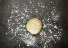 Lump of dough on work surface sprinkled with flour. Lump of dough on gray work surface sprinkled with flour stock image