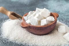 Lump and granulated refined sugar. On the wooden background royalty free stock photo