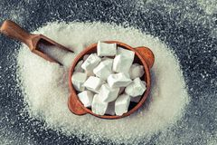 Lump and granulated refined sugar. On the wooden background stock image