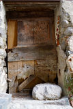 Lump of rock in front of an old morbid door. In Eus, France Royalty Free Stock Photography