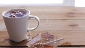 Lump sugar falling to cup of tea and splashing. Unhealthy eating and drinks concept - lump sugar falling to cup of tea and splashing all over wooden table stock video