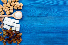 Lumps and sanding sugar for sweets on blue kitchen table background top view mock up Royalty Free Stock Photo