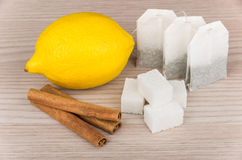 Lumps of sugar, cinnamon sticks, lemon and packets of tea Stock Image