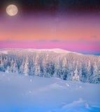 Luna in aumento sopra le montagne gelide di inverno immagine stock