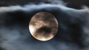 Luna bianca che splende dietro uno strato sottile delle nuvole fotografie stock libere da diritti