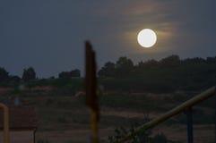 Luna che aumenta sopra la collina Immagine Stock
