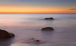 Luna crescente ad alba con il bello cielo rosso, mare calmo con le rocce in priorità alta, nou del porto, bona di cala, Mallorca, immagini stock libere da diritti