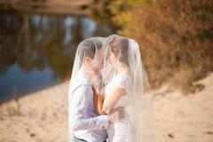 Luna de miel apenas de la pareja casada de la boda novia feliz, novio que se coloca en la playa, besándose, sonriendo, riendo, di Fotografía de archivo libre de regalías