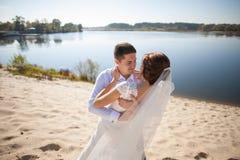 Luna de miel apenas de la pareja casada de la boda novia feliz, novio que se coloca en la playa, besándose, sonriendo, riendo, di Imagenes de archivo