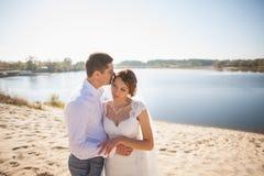 Luna de miel apenas de la pareja casada de la boda novia feliz, novio que se coloca en la playa, besándose, sonriendo, riendo, di Foto de archivo libre de regalías