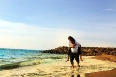 Luna de miel de los pares en la playa Foto de archivo