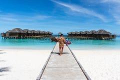 Luna de miel en Maldivas Sirva detener a su esposa en los brazos en el puente en la playa del océano Fotografía de archivo libre de regalías