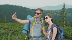 Luna de miel feliz Un par joven se fotografía en las montañas, junto en un alza almacen de video
