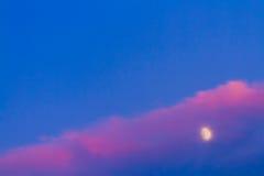 Luna debajo de la nube rosada en el cielo azul fotografía de archivo