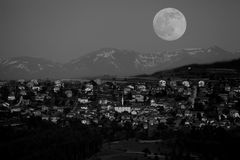 Luna del Bw sobre el pequeño pueblo Fotografía de archivo libre de regalías