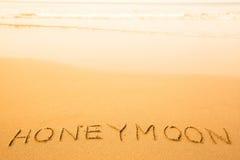 Luna di miele, testo scritto in sabbia su una spiaggia Fotografie Stock