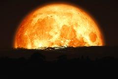 luna eccellente del sangue indietro sulla montagna della siluetta sul cielo notturno immagini stock libere da diritti