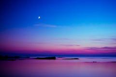 Luna en el fondo de la puesta del sol foto de archivo