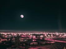 Luna Llena en el cielo oscuro sobre ciudad iluminada con las luces rojas fotos de archivo libres de regalías