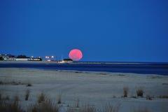Luna Llena enorme que sube sobre la playa Imagen de archivo libre de regalías