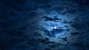Luna Llena que cruza el cielo nocturno detrás de las nubes almacen de video