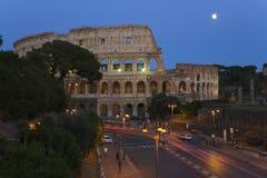 Luna Llena que sube sobre el Colosseum o Roman Coliseum en la oscuridad con las luces rayadas del coche, originalmente Flavian Am Fotografía de archivo