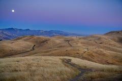 Luna Llena que sube sobre las colinas de oro, según lo visto de pico de la misión, área de la Bahía de San Francisco, California foto de archivo