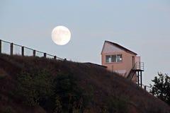Luna Llena sobre el horizonte y las montañas de mar fotografía de archivo libre de regalías