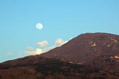 Luna Llena sobre el horizonte y las montañas de mar fotos de archivo