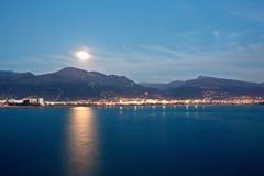 Luna Llena sobre el horizonte y las montañas de mar imagenes de archivo