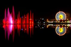 Luna park  and city reflection. Carousels wheel and city and reflection at night in city. Water show and reflection. Beautiful colored water show with fountains Royalty Free Stock Photos