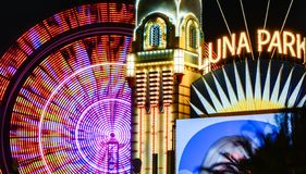 Luna Park with Ferris wheel. Luna Park Sydney Entrance, Australia, illuminated at night - with the blurred illustration of a spinning Ferris wheel in the royalty free stock images