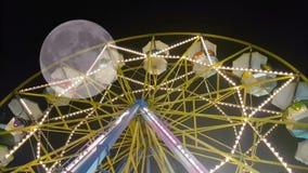 Luna park groot wiel met mensen tegen de volle maan Een surrealistische mening stock videobeelden