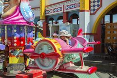 Luna Park - Melbourne. St Kilda, Melbourne, Australia: March 18, 2017: A little girl rides a carousel at Melbourne`s Luna Park. The historic amusement park is Stock Images