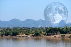 luna piena del latte indietro sulla montagna e sul fiume della siluetta fotografia stock libera da diritti