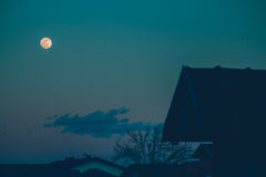 Luna piena sopra i tetti Immagini Stock Libere da Diritti