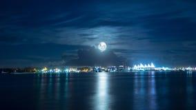 Luna piena sopra la città luminosa Fotografie Stock