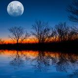 Luna piena sopra un lago di sera Immagine Stock