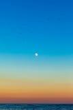 Luna piena su un cielo dell'arcobaleno Fotografie Stock
