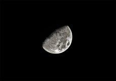 Luna quarta del primo piano sul cielo nero Fotografie Stock Libere da Diritti