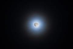 Luna que brilla a través de las nubes que hacen un halo imágenes de archivo libres de regalías