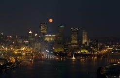 Luna que se levanta encima hacia el centro de la ciudad Imágenes de archivo libres de regalías