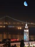 Luna sobre el edificio del transbordador y el puente de la bahía Fotografía de archivo