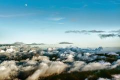 Luna sobre las montañas cubiertas en nubes Fotos de archivo