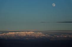 Luna sobre los picos de montaña Foto de archivo libre de regalías