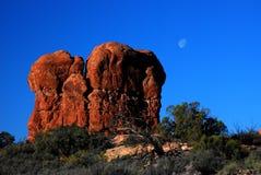 Luna sobre roca del desierto en la salida del sol Imagen de archivo libre de regalías
