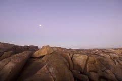 Luna sopra l'oceano e le rocce Immagini Stock